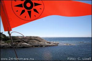 Foto på den orangea 24 timmars vimpeln med ett skär i bakgrunden. Foto: Christian Lizell.