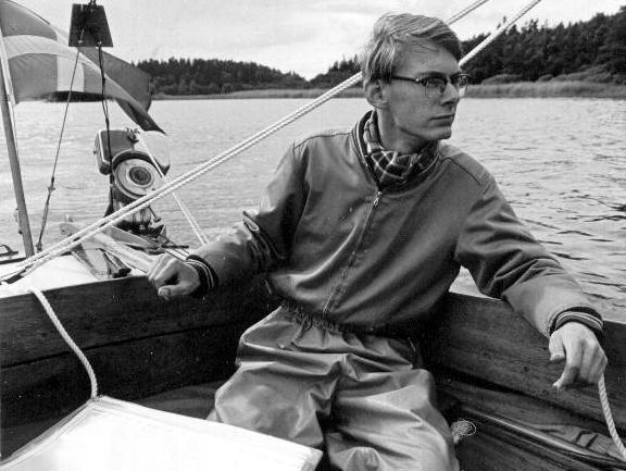 Svartvitt foto på ung Christer Forsgren i sittbrunnen på en träbåt.