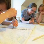Foto på tre kvinnor som studerar ett sjökort ingående under en torrsegling.