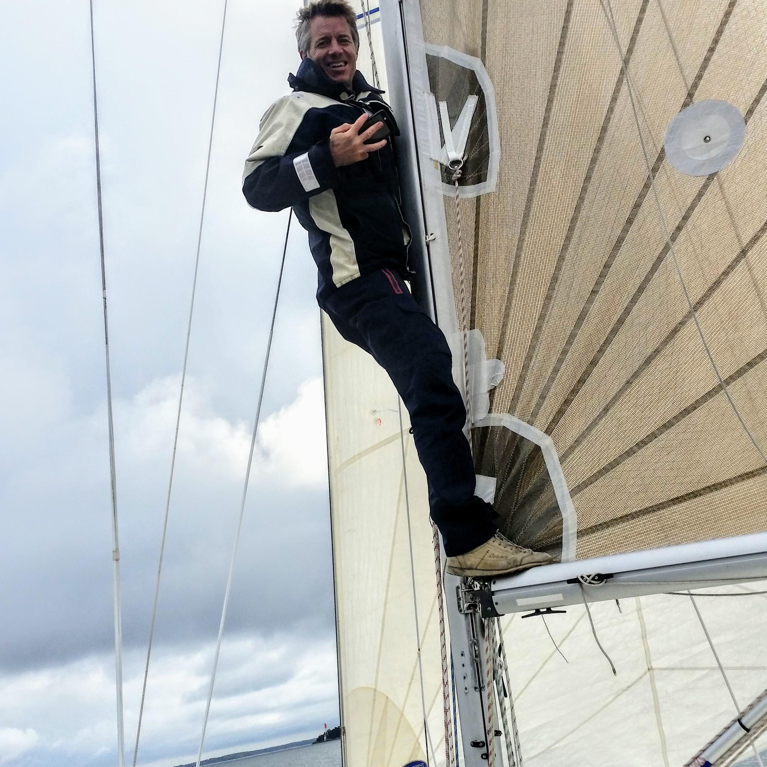 Fotograferande man klättrar på bommen under segling